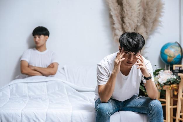 Dwóch młodych mężczyzn było wściekłych na łóżku, a drugi siedział na skraju łóżka i był zestresowany.