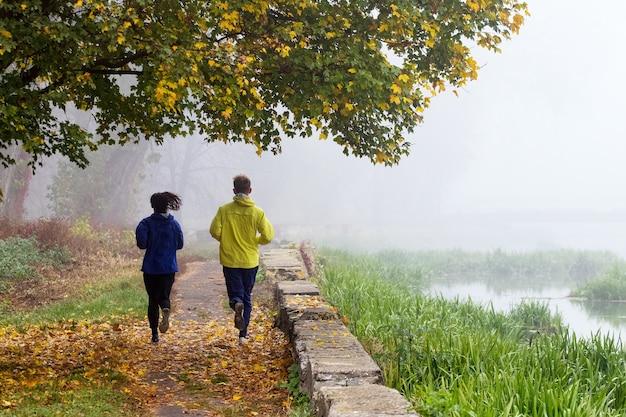 Dwóch młodych mężczyzn, chłopak i dziewczyna, mają poranny bieg w jesiennym parku. poranna mgła w parku.