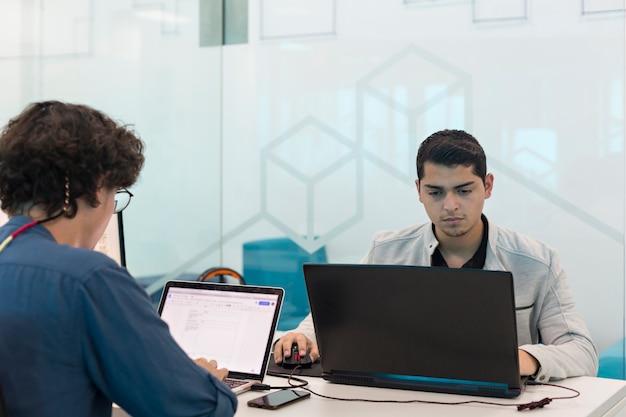 Dwóch młodych mężczyzn pracujących przy komputerze w biurze coworkingowym.