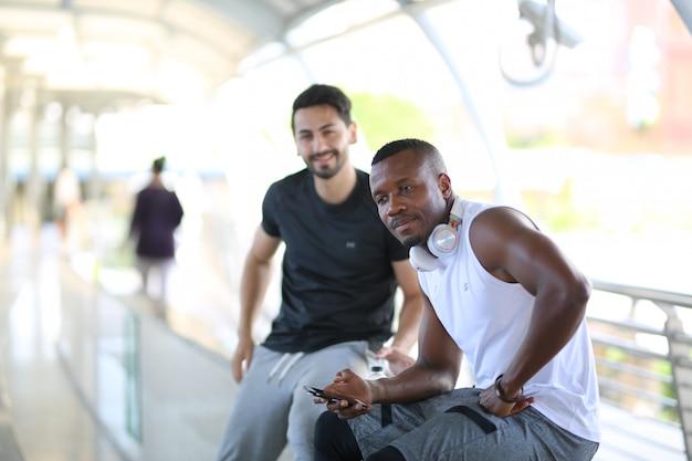 Dwóch młodych mężczyzn siedzących przy relingu po joggingu