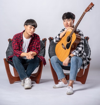 Dwóch młodych mężczyzn siedzi na krześle, trzymając gitarę