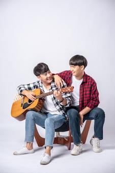 Dwóch młodych mężczyzn siedziało na krześle i grało na gitarze.