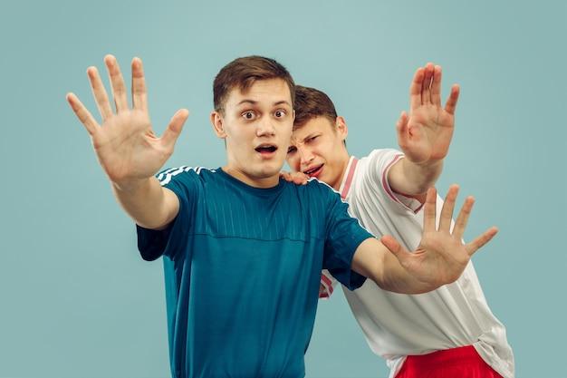 Dwóch młodych mężczyzn stojących w odzieży sportowej na białym tle. miłośnicy sportu, klubu lub drużyny piłkarskiej. portret przyjaciół w połowie długości. pojęcie ludzkich emocji, wyraz twarzy.