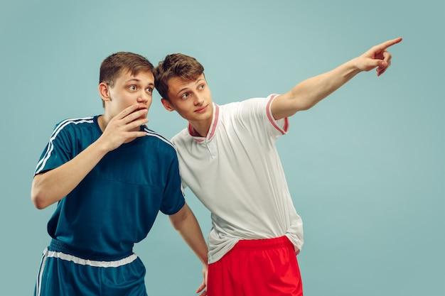 Dwóch młodych mężczyzn stojących w odzieży sportowej na białym tle. wskazując i zszokowany. portret w połowie długości pięknych modelek. pojęcie ludzkich emocji, wyraz twarzy. przedni widok.