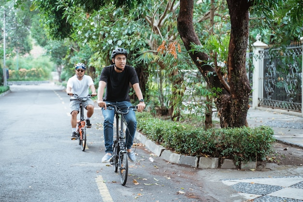 Dwóch młodych mężczyzn w hełmach lubi wspólnie jeździć na rowerach