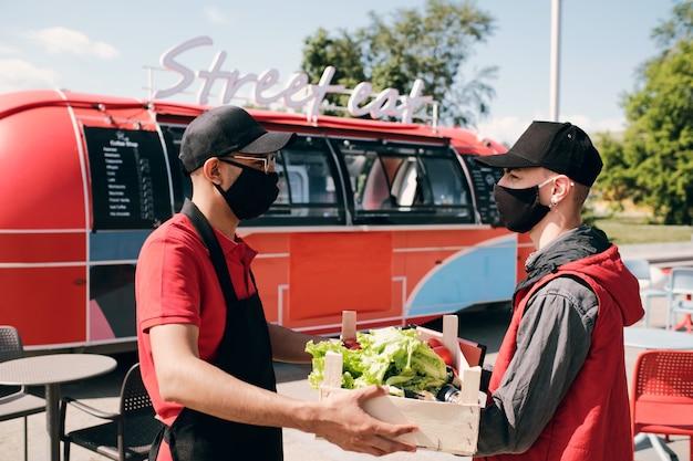 Dwóch młodych mężczyzn w maskach ochronnych trzymających drewniane pudełko ze świeżymi warzywami
