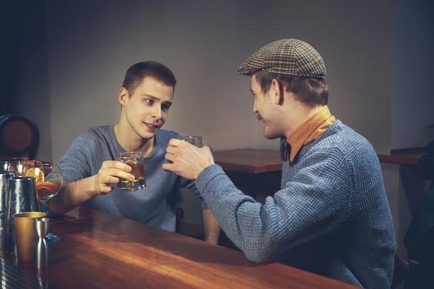 Dwóch młodych mężczyzn w zwykłych ubraniach rozmawia, siedząc przy barze w pubie