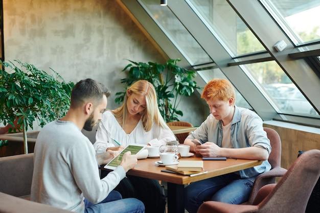 Dwóch młodych mężczyzn za pomocą gadżetów i mądra dziewczyna robi notatki w notatniku przy stole w kawiarni uczelni podczas odrabiania lekcji