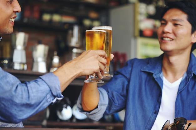 Dwóch młodych mężczyzn zderzających się z dwiema szklankami piwa, aby świętować swój sukces.