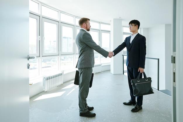 Dwóch młodych, międzykulturowych partnerów biznesowych w strojach wizytowych, stojących naprzeciw siebie i uściskających dłonie na korytarzu w centrum biurowym