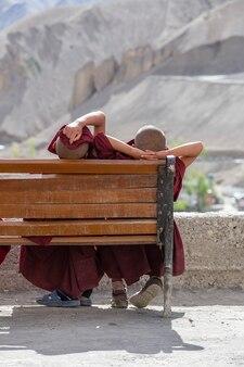 Dwóch młodych mnichów buddyjskich odpoczywa na ławce w słoneczny dzień na ulicy obok górskiego klasztoru lamayuru w ladakh w północnych indiach