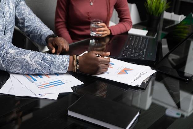 Dwóch młodych murzynów rozmawia o swoim biznesie za pomocą diagramów siedzi przy biurku w biurze