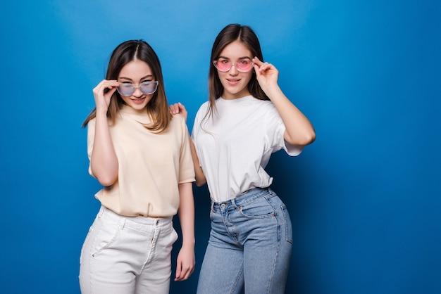 Dwóch młodych najlepszych przyjaciół, obejmując na niebieskiej ścianie. młode kobiety świetnie się razem bawią.