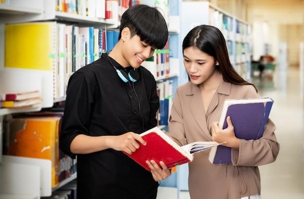 Dwóch młodych nastolatków rozmawiających i czytających razem książkę, szukających danych do egzaminu, w bibliotece, wokół rozmazanego światła