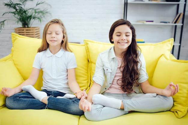 Dwóch młodych nastolatków siedzą w pozycji lotosu na żółtej kanapie w pokoju. medytują. dziewczyny wyrażają pozytywne emocje. trzymają oczy zamknięte.