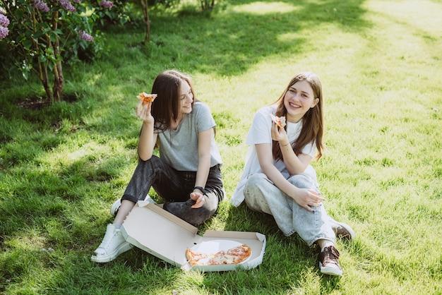 Dwóch młodych nastoletnich przyjaciół zabawy w parku na trawie i jedzenia pizzy. kobiety jedzą fast foody. nie zdrowa dieta. miękka selektywna ostrość.