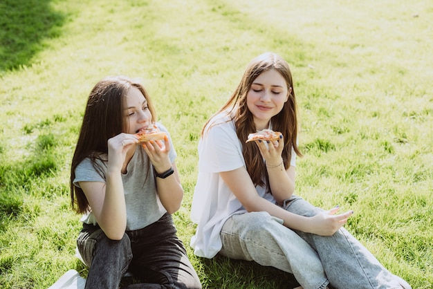 Dwóch młodych nastoletnich przyjaciół zabawy w parku na trawie i jedzenie pizzy. kobiety jedzą fast foody. nie zdrowa dieta. miękka selektywna ostrość.