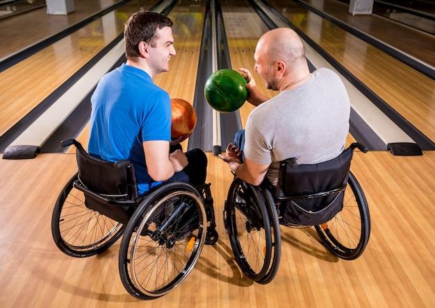 Dwóch młodych niepełnosprawnych mężczyzn na wózkach inwalidzkich grających w kręgle w klubie