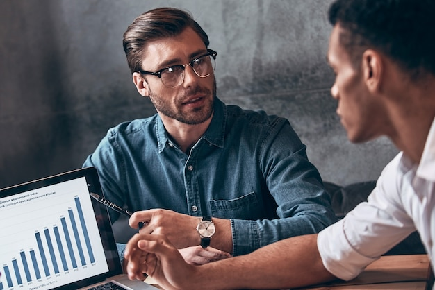 Dwóch młodych nowoczesnych mężczyzn w eleganckiej odzieży codziennej analizujących dane na laptopie podczas pracy w biurze