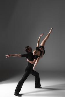 Dwóch młodych nowoczesnych tancerzy baletowych na szarej ścianie