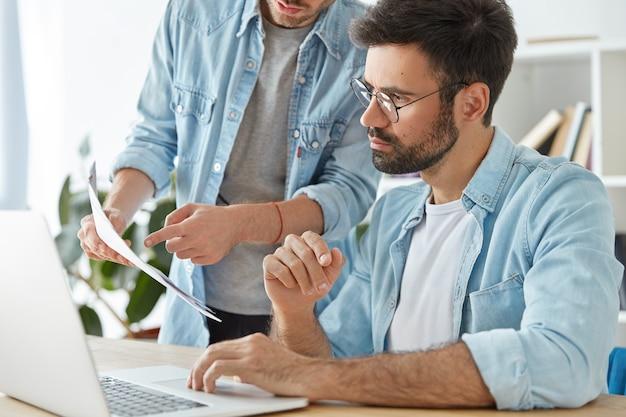 Dwóch młodych, odnoszących sukcesy pracowników biznesowych współpracuje w przestrzeni coworkingowej