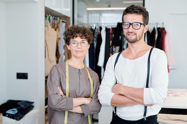Dwóch młodych, pewnych siebie projektantów mody i krawców ze skrzyżowanymi rękami, stojących w warsztacie