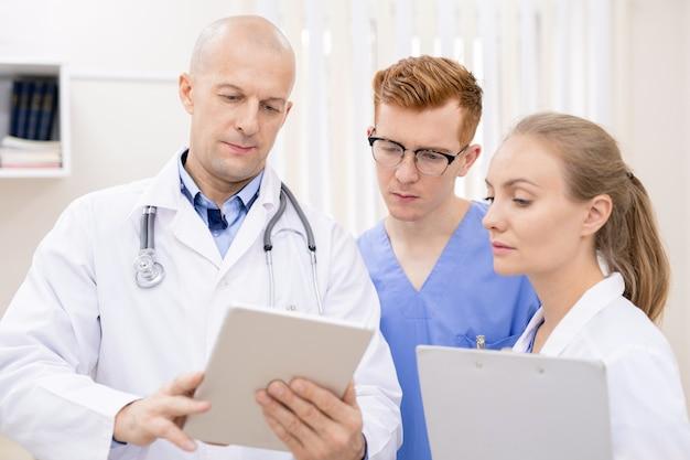 Dwóch młodych, poważnych stażystów uważnie słucha pewnego siebie lekarza, patrząc na informacje na ekranie panelu dotykowego