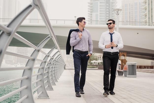 Dwóch młodych, pracowitych biznesmenów w garniturze spacerując po dubai marine i rozmawiając o sytuacji biznesowej w swoim biurze.