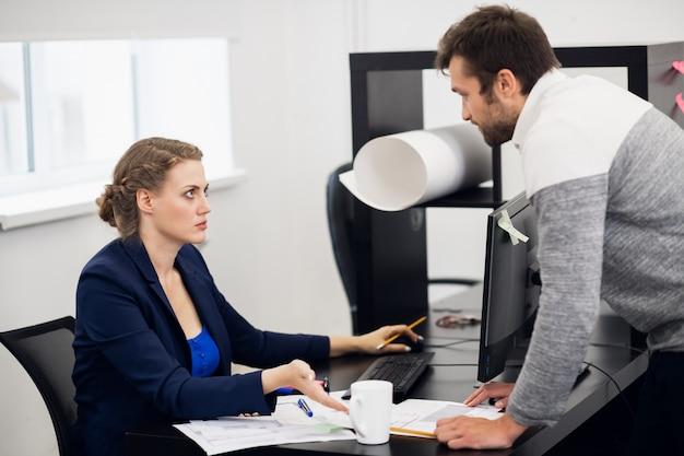Dwóch młodych pracowników biurowych omawia coś w swoim miejscu pracy