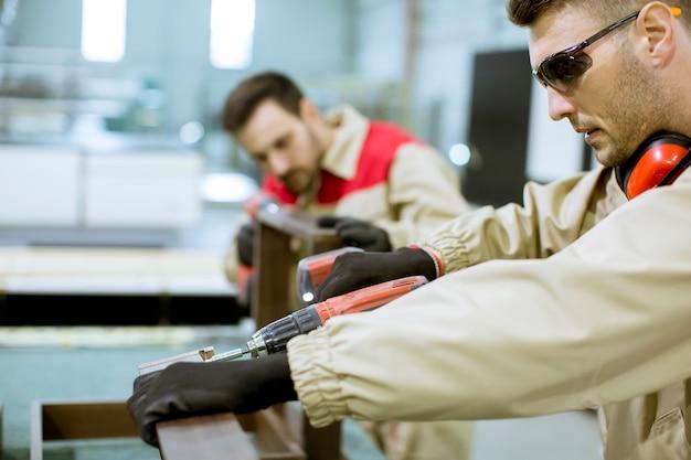 Dwóch młodych pracowników montujących meble w fabryce