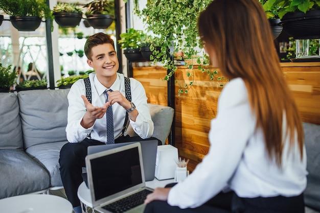 Dwóch młodych pracowników planuje dzień. omów kwestie związane z pracą. usiądź przy stole