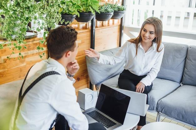 Dwóch młodych pracowników planuje dzień. omów problemy związane z pracą. usiądź przy stole w eleganckiej przestrzeni w surowej sukience z laptopem