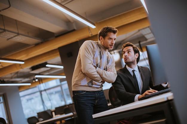 Dwóch młodych pracowników pracujących w biurze