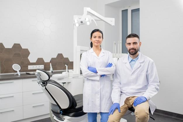 Dwóch młodych profesjonalnych dentystów w rękawiczkach i białych fartuchach patrzy na ciebie z miejsca pracy ze sprzętem medycznym