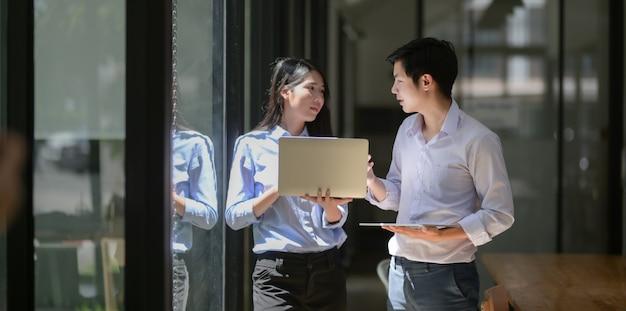 Dwóch młodych profesjonalnych partnerów biznesowych wspólnie omawiających swój projekt