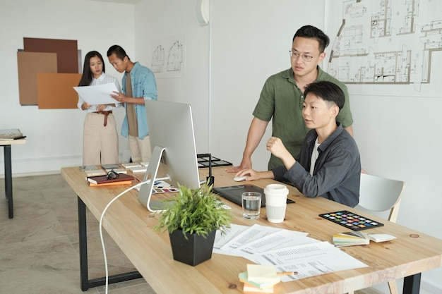 Dwóch młodych projektantów patrzących na ekran komputera