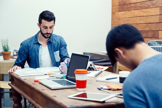 Dwóch młodych przedsiębiorców przygotowujących swój nowy projekt biznesowy w nowoczesnej przestrzeni coworkingowej