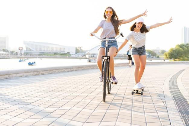Dwóch młodych przyjaciół odpoczywa w upalny letni dzień z jedną młodą kobietą jadącą na rowerze i holującą przyjaciółkę na deskorolce w dół miejskiej ulicy.