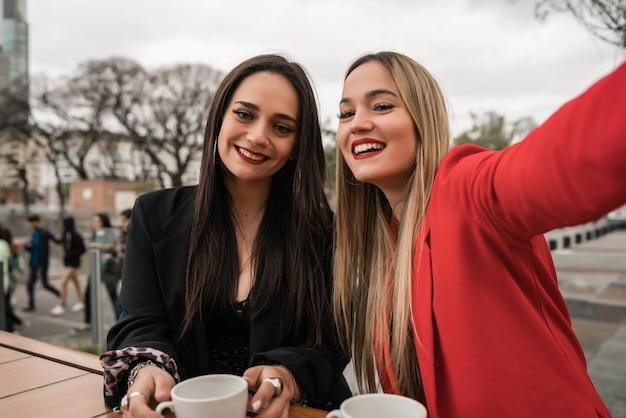 Dwóch młodych przyjaciół razem przy selfie w kawiarni
