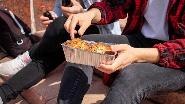 Dwóch młodych przyjaciół siedzących na schodach w parku i jedzących
