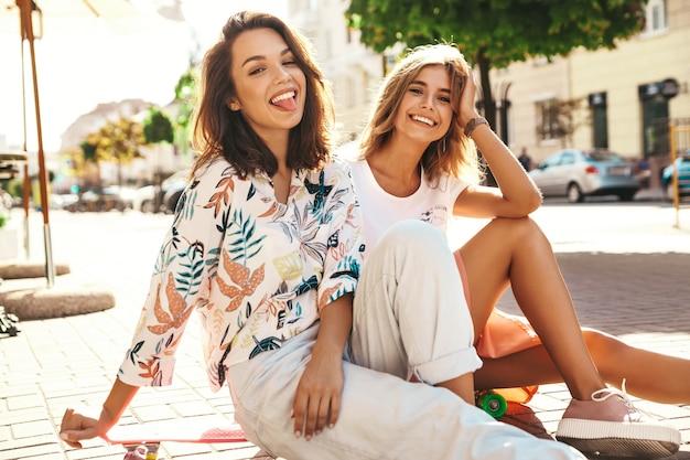 Dwóch młodych przyjaciół siedzi na deskorolce grosza na ulicy, pokazując język