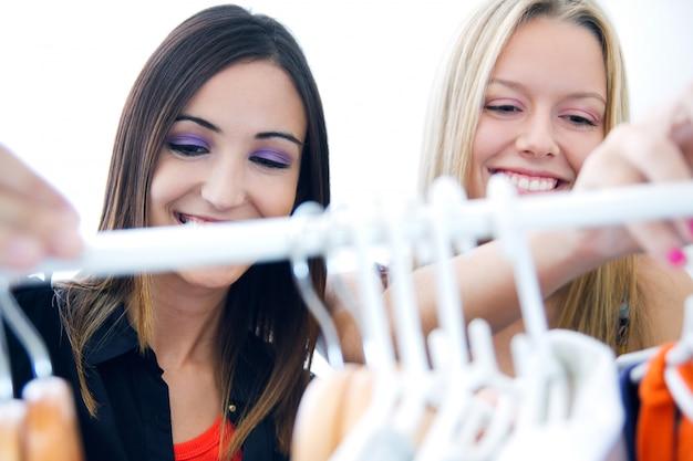 Dwóch młodych przyjaciół szukających ubrań w sklepie