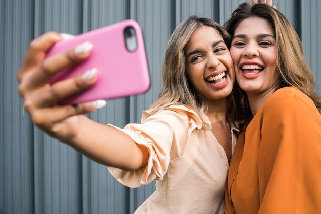 Dwóch młodych przyjaciół uśmiecha się i robi selfie z telefonem komórkowym, stojąc na zewnątrz