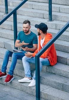 Dwóch młodych przyjaciół w ubranie ze smartfonów i laptopa na schodach na zewnątrz
