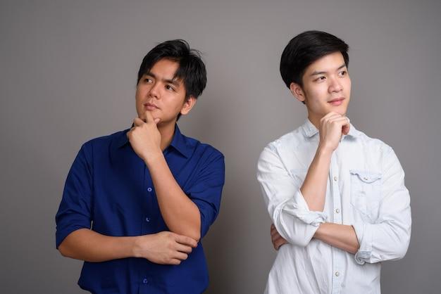 Dwóch młodych przystojnych mężczyzn z azji na szaro