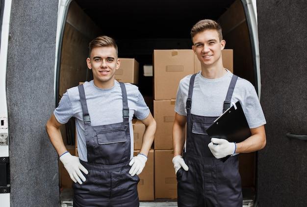 Dwóch młodych przystojnych uśmiechniętych pracowników w mundurach stoi przed furgonetką pełną pudeł