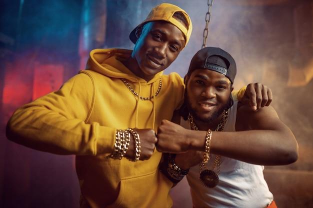 Dwóch młodych raperów tańczy breakdance z fajną undergroundową dekoracją. wykonawcy hip-hopu, modni rapujący, breakdance