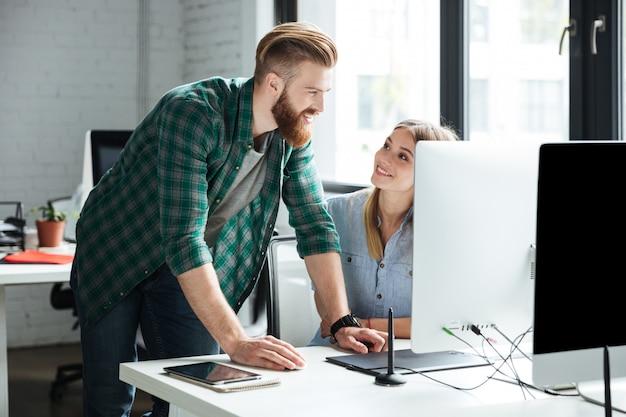 Dwóch młodych skoncentrowanych kolegów pracuje w biurze
