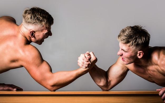Dwóch młodych sportowców stacza ostry pojedynek siłowania się na rękę.