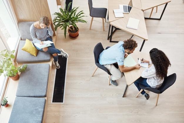 Dwóch młodych startupowców siedzących przy stole w przestrzeni coworkingowej rozmawiających o projekcie zespołowym, przeglądających informacje. dziewczyna siedzi na parapecie, szykując się do egzaminów.